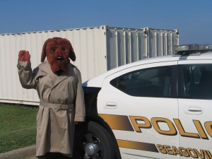 McGruff the Dog stands next to a police car